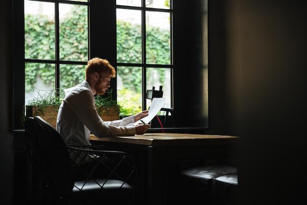 Foto del empresario barbudo con cabeza lectora concentrada leyendo contrato, sentado en la cafetería
