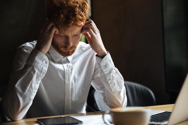 Foto del empresario pelirrojo cansado, tocando su cabeza, mirando la tableta digital