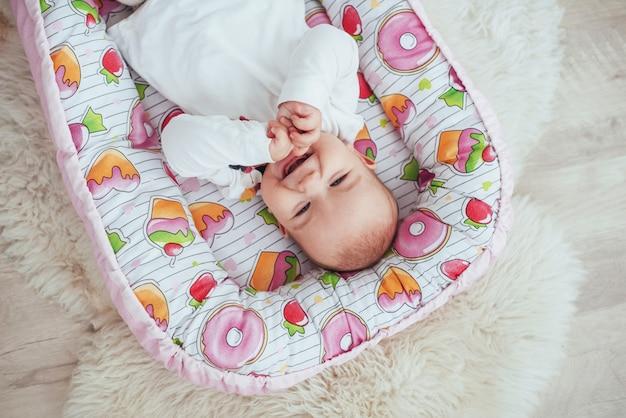 Foto encantador bebé recién nacido en una cuna rosa