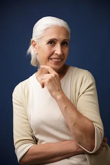 Foto de encantadora mujer madura en camiseta beige, sosteniendo su barbilla