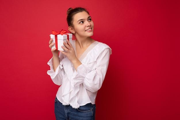 Foto de encantadora mujer morena joven sonriente feliz aislada sobre fondo rojo pared vistiendo blusa blanca sosteniendo caja de regalo blanca con cinta roja y mirando hacia el lado.