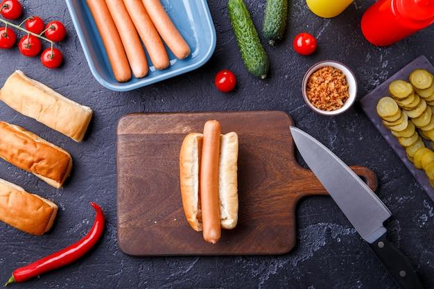 Foto encima de perritos calientes en la tabla de cortar en la mesa con salchichas
