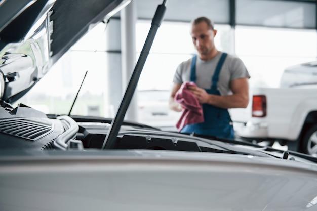 Foto enfocada. hombre de uniforme azul trabaja con coche roto. haciendo reparaciones