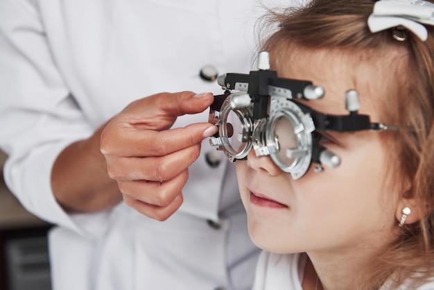 Foto enfocada del niño en foróptero que prueba sus ojos en el consultorio del médico.