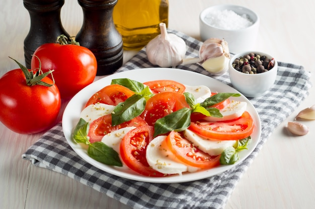 Foto de ensalada caprese con tomate, albahaca, mozzarella, aceitunas y aceite de oliva.