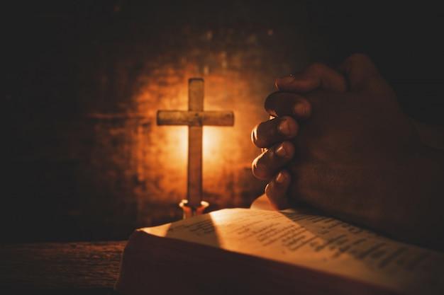 Foto de época de la mano con la biblia orando.