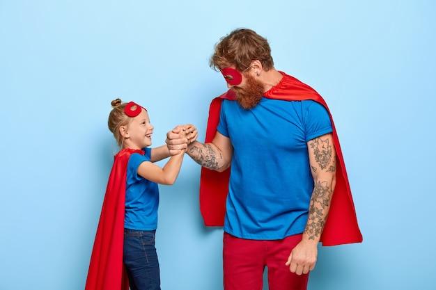 Foto del equipo familiar encantado de superhéroes, la pequeña hija de jengibre y el padre mantienen las manos juntas