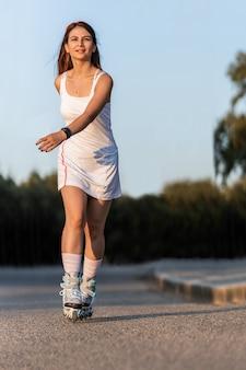 Foto con espacio de copia de una mujer en vestido patinando con patines en línea al aire libre
