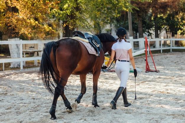 Foto de la espalda, mujer joven con uniforme especial y casco con su caballo de montar.