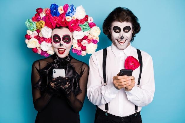 Foto de espeluznante zombi dos personas hombre dama sostener teléfonos emocionado encontrar tienda en línea poción de inmortalidad vestir vestido negro traje de muerte rosas diadema tirantes fondo de color azul aislado