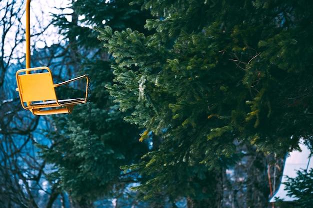 Foto estilística de la vieja silla elevadora de esquí vacía amarilla grunged vintage aislada a la izquierda, ramas de pino bahinf en bosque de invierno, foco en el asiento