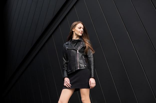 Foto de estilo de moda de mujer joven hermosa en la pared de fondo negro