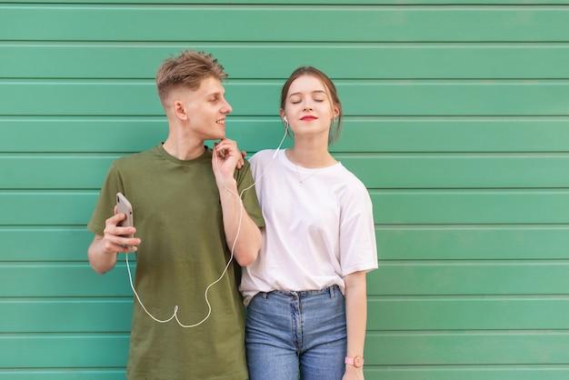 Foto de estilo de vida chica atractiva y un chico guapo escuchando música en los auriculares