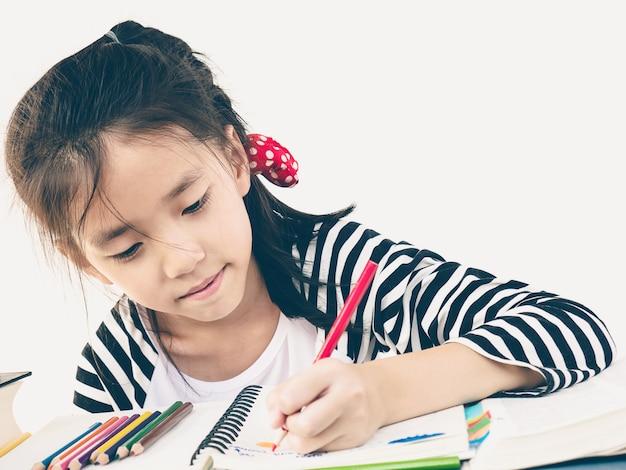 Foto de estilo vintage de una niña está felizmente coloreando un libro