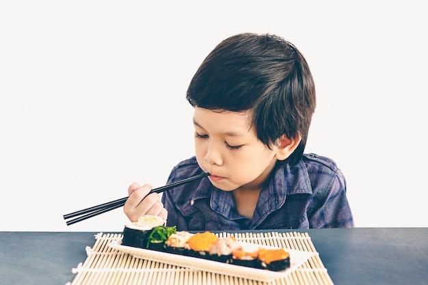 Foto de estilo vintage de niño encantador asiático está comiendo sushi