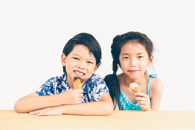 Foto de estilo vintage de niños asiáticos comiendo helado.