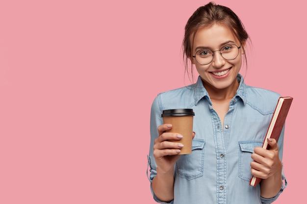 Foto de estudiante alegre tiene diario rojo y café para llevar, sonríe positivamente