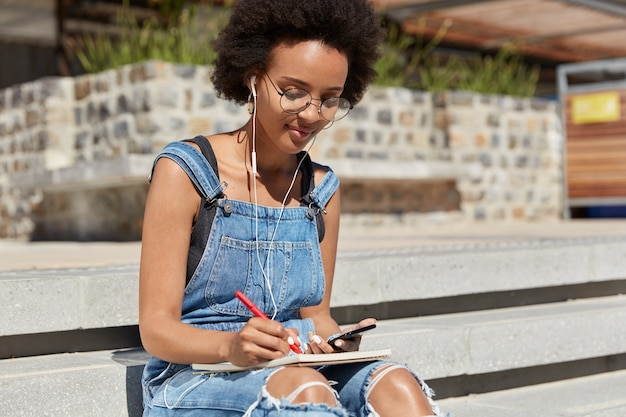 Foto de estudiante escucha audiolibro con auriculares y teléfono móvil, escribe algunos registros y detalles en el diario, posa en las escaleras al aire libre, se prepara para el seminario, usa internet y tecnología.