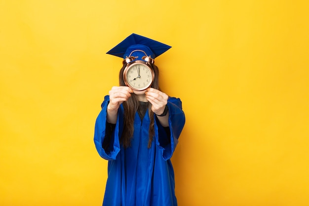 Una foto de una estudiante que acaba de graduarse sosteniendo un pequeño reloj en la fuente de su rostro cerca de una pared amarilla