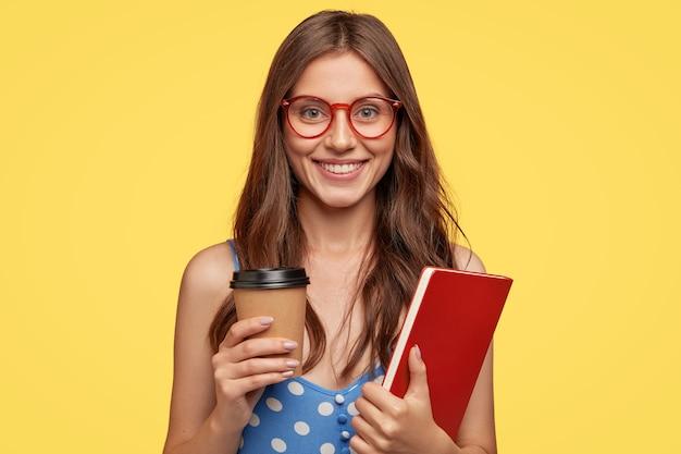 Foto de una estudiante universitaria alegre que lleva un libro de ejercicios y toma un café, sonríe ampliamente, está de buen humor después de las conferencias, se regocija en las próximas vacaciones, modelos contra la pared amarilla