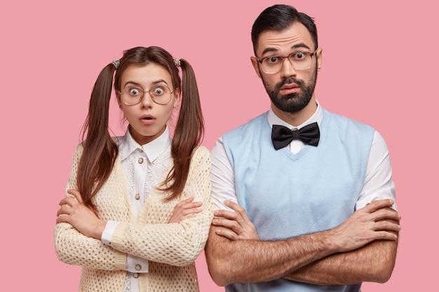 Foto de estudiantes universitarios estupefactos, los nerds mantienen los brazos cruzados, miran con ojos saltones, vestidos con ropa antigua de moda