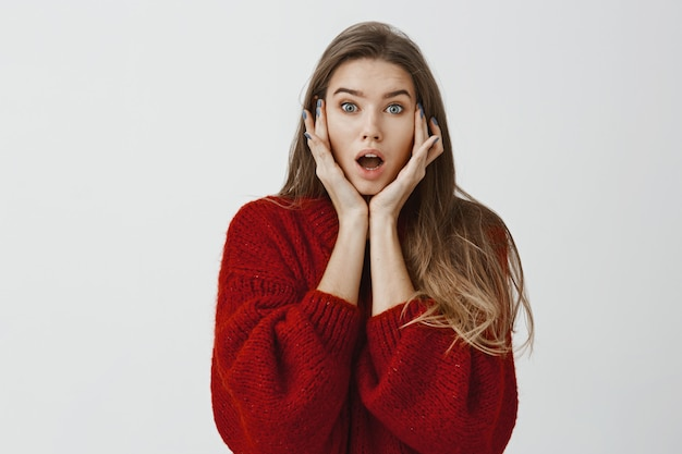 Foto de estudio de la abrumada y atractiva novia europea con suéter rojo suelto, con las palmas de las manos en las mejillas y la mandíbula caída, escuchando noticias o rumores impactantes, jadeando sobre la pared gris
