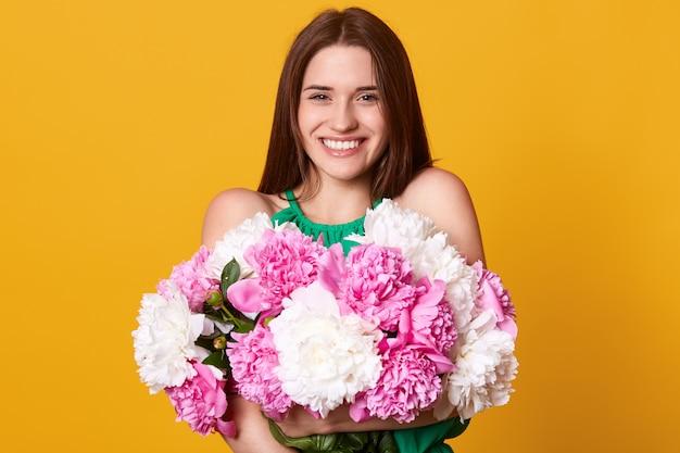 Foto de estudio de la alegre niña brillante, se ve feliz, se encuentra con una sonrisa dentuda, morena joven con ramo de peonías blancas y rosas