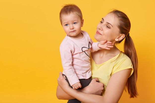 Foto de estudio de amorosa madre sosteniendo a su bebé