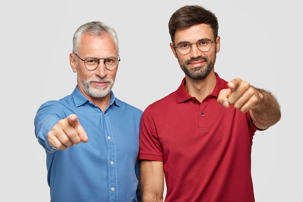 Foto de estudio de un anciano y un adulto macho barbudo de pie uno al lado del otro en el interior
