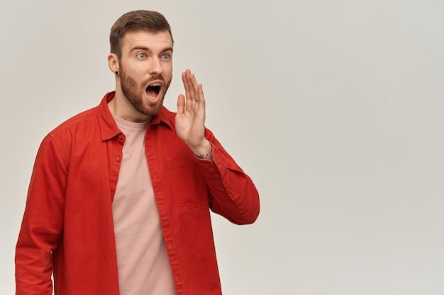 Foto de estudio de apuesto joven barbudo en camisa roja de pie y gritando a distancia sobre la pared blanca