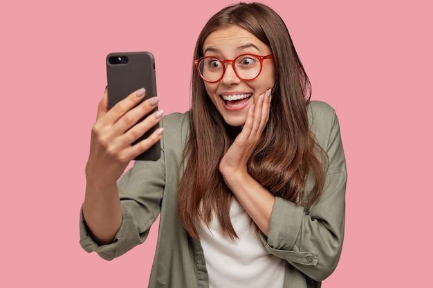 Foto de estudio de asombrada joven mujer caucásica con expresión positiva, hace selfie con teléfono celular
