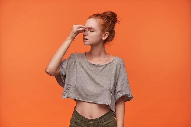 Foto de estudio de atractiva joven cansada en ropa casual sosteniendo su puente de la nariz con la mano, posando sobre fondo naranja con los ojos cerrados, vistiendo su pelo rojo en un nudo