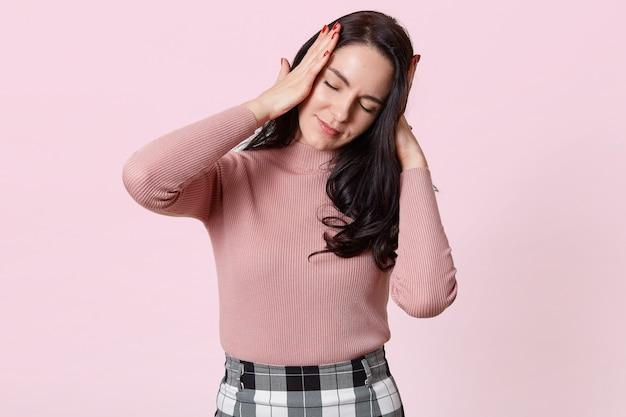 Foto de estudio de atractiva joven con terrible dolor de cabeza, mantiene ambas manos sobre la cabeza, necesita tomar medicamentos, mujer morena con camisa rosa y falda a cuadros, aislado en rosa