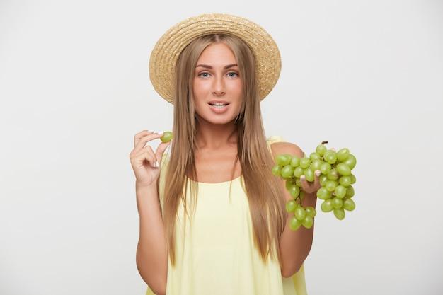 Foto de estudio de bastante joven mujer rubia de ojos azules con maquillaje natural manteniendo uvas verdes en manos levantadas mientras mira a cámara con cara tranquila, de pie sobre fondo blanco