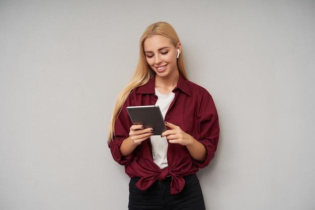 Foto de estudio de bella joven rubia con cabello suelto posando sobre fondo gris claro con tablet pc en manos levantadas y sonriendo sinceramente, vestida con ropa casual