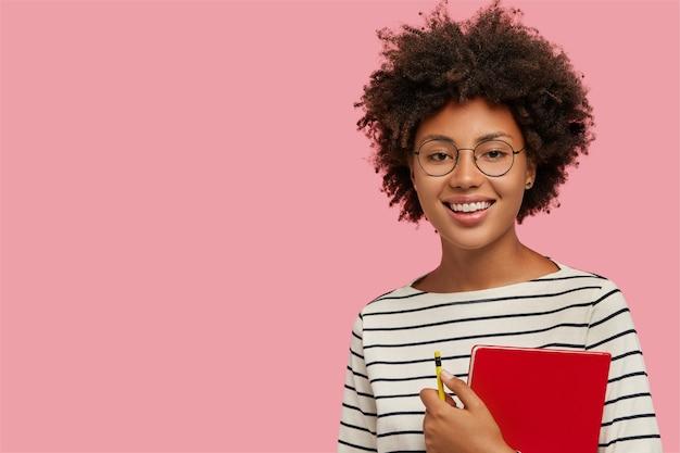 Foto de estudio de chica de piel muy oscura con una sonrisa suave, se prepara para las clases, lleva el bloc de notas rojo y lápiz