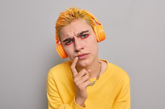 Foto de estudio de una chica punk atenta con peinado amarillo, maquillaje brillante, que mantiene el dedo índice cerca de los labios, intenta ver algo, escucha información con expresión concentrada, vestida de manera informal, posa interior