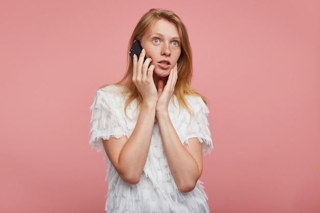 Foto de estudio de una dama pelirroja bastante joven con los ojos abiertos sosteniendo la palma en su rostro mientras posa sobre un fondo rosa, mirando con sorpresa hacia adelante mientras tiene una conversación telefónica