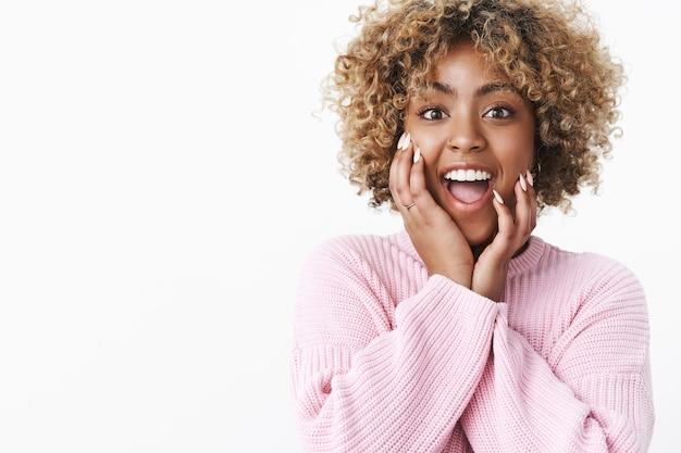 Foto de estudio de divertida y emocionada mujer africana guapa con cabello rizado rubio sonriendo y dejando caer la mandíbula de asombro tomados de la mano en las mejillas de pie emocionado sobre la pared blanca