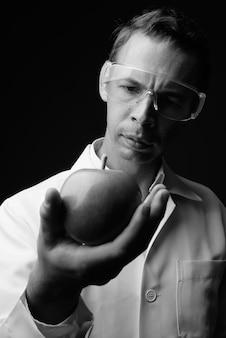 Foto de estudio de doctor hombre con gafas protectoras contra la pared gris en blanco y negro