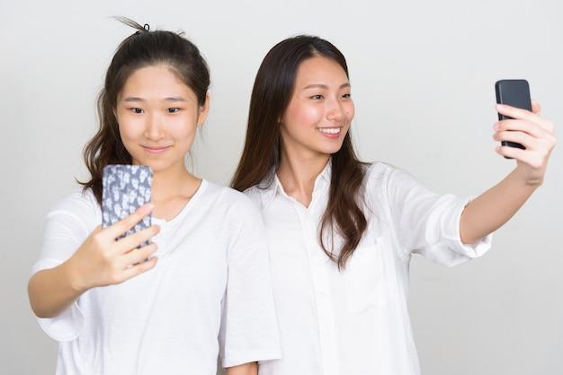 Foto de estudio de dos jóvenes hermosas mujeres coreanas como amigos juntos contra el fondo blanco.