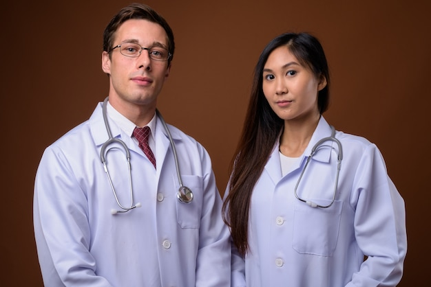 Foto de estudio de dos jóvenes médicos juntos contra backgrou marrón