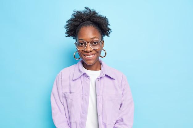 Foto de estudio de encantadora estudiante de piel oscura sonríe ampliamente disfruta del día libre mira con alegría a la cámara