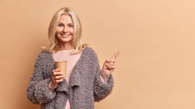 Foto de estudio de la encantadora mujer rubia de cincuenta años sonríe positivamente sostiene un vaso de papel desechable de bebida caliente viste abrigo de piel indica distancia aislada sobre pared marrón