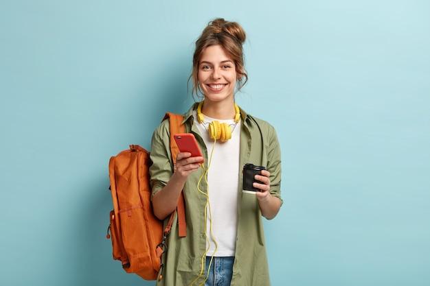 Foto de estudio de una estudiante alegre que toma un café después de las conferencias, escucha un audiolibro en auriculares, disfruta del registro del sitio web, usa el teléfono móvil para chatear en línea, tiene una mochila en la espalda.