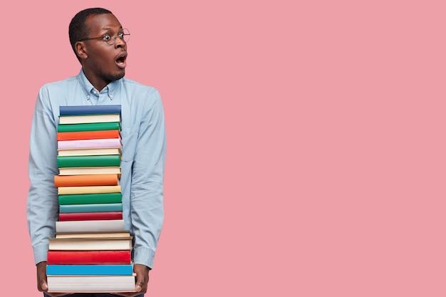 Foto de estudio de estupefacto profesor varón negro de piel oscura, tiene muchos libros perfectamente organizados, se prepara para el seminario o la realización de una conferencia