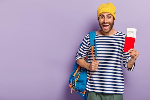 Foto de estudio de feliz mochilero masculino sin afeitar sostiene el pasaporte con el documento, lleva la mochila al hombro, sonríe con alegría, vestido con ropa informal, aislado sobre la pared púrpura, listo para el viaje
