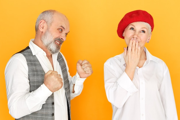 Foto de estudio de frívola despreocupada mujer de mediana edad en boina roja que cubre la boca jadeando, chico barbudo enojado apretando los puños, con mirada furiosa y loca, va a golpear a su esposa. violencia doméstica