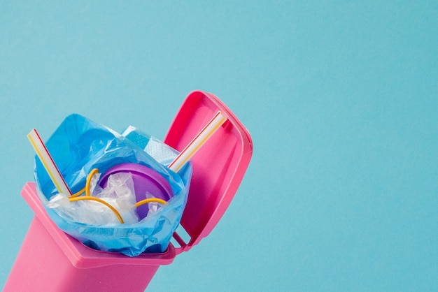 Foto de estudio de una gran basura rosa sobre fondo azul.