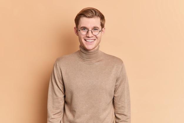 Foto de estudio de guapo adolescente sonríe agradablemente tiene feliz hablar lleva gafas redondas transparentes y poloneck